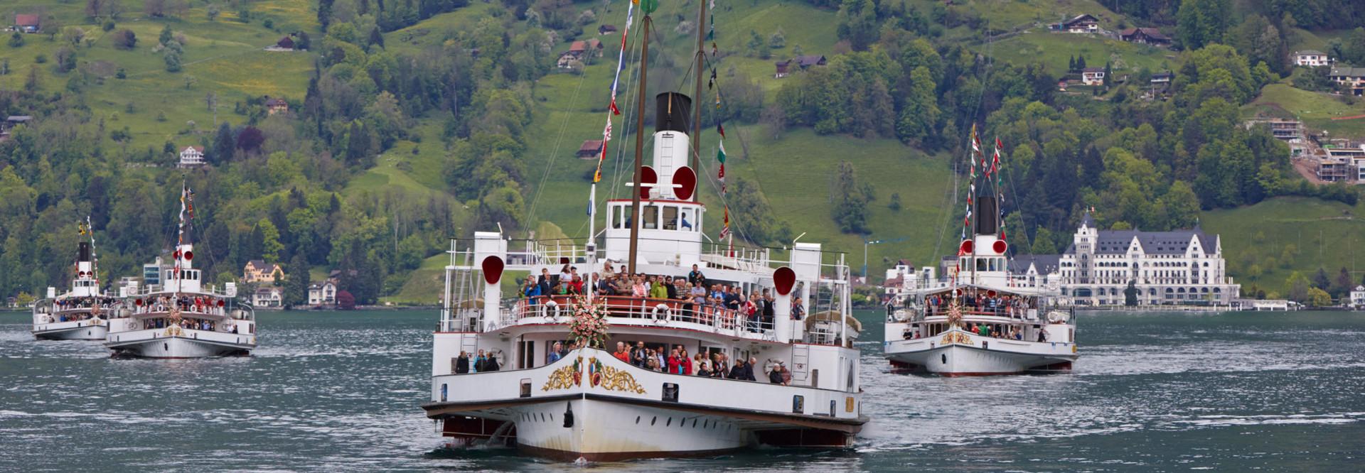 Vier Dampfschiffe mit Festbeflaggung an einer Parade