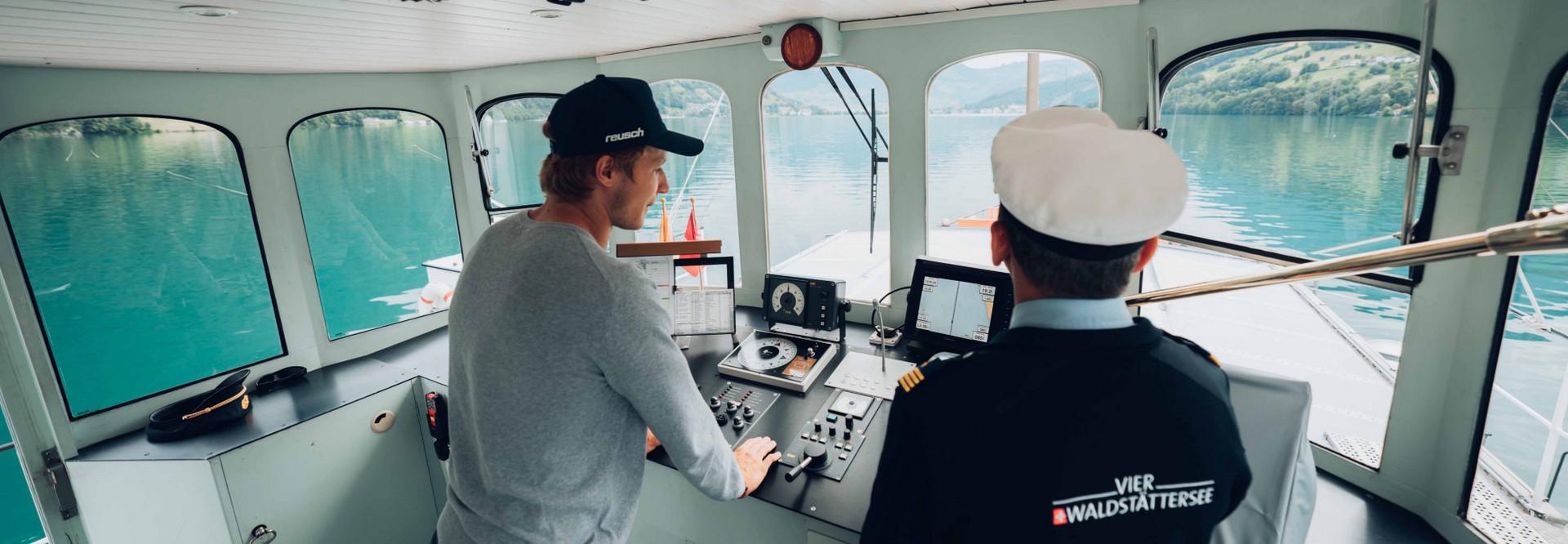 Marco Odermatt steht links neben dem Kapitän im Steuerhaus, schaut auf die Karte und stützt sich ab.