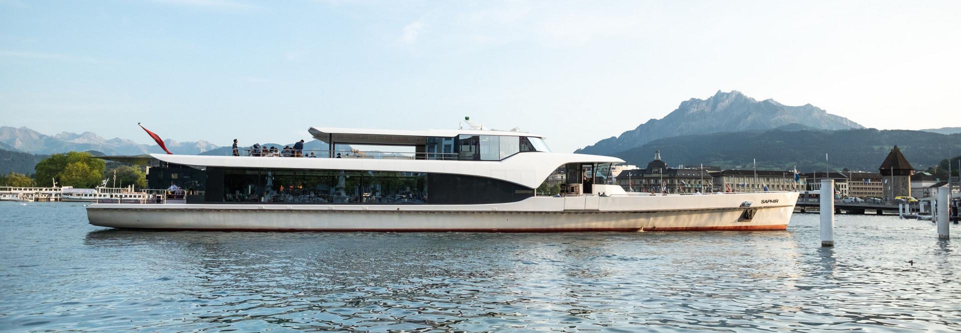 Das Motorschiff Saphir fährt Richtung Steg 7 in Luzern. Im Hintergrund ist der Wasserturm sowie der Pilatus zu sehen.