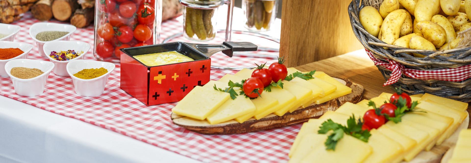 Ein Buffet mit feinem Raclette Käse und Beilagen wie Kartoffeln