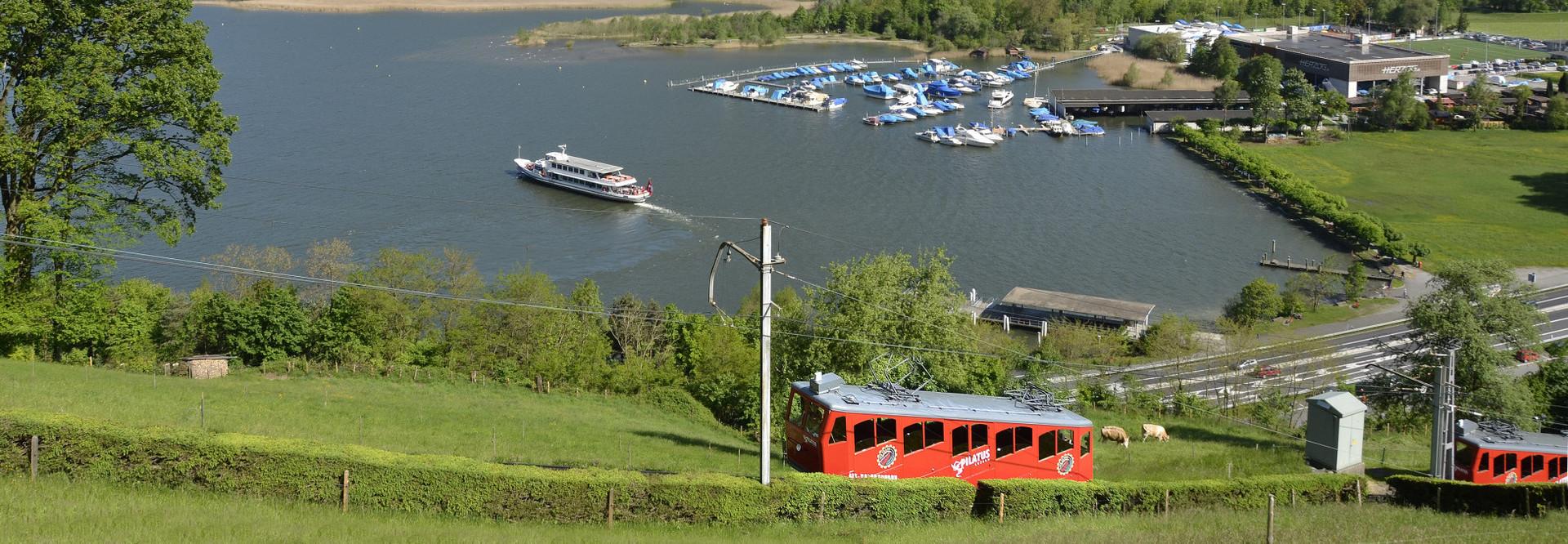 Rote Standseilbahn vom Pilatus, welche von Alpnachstad losfährt. Im Hintegrund der Vierwaldstättersee mit einem Schiff und dem Stanserhorn.
