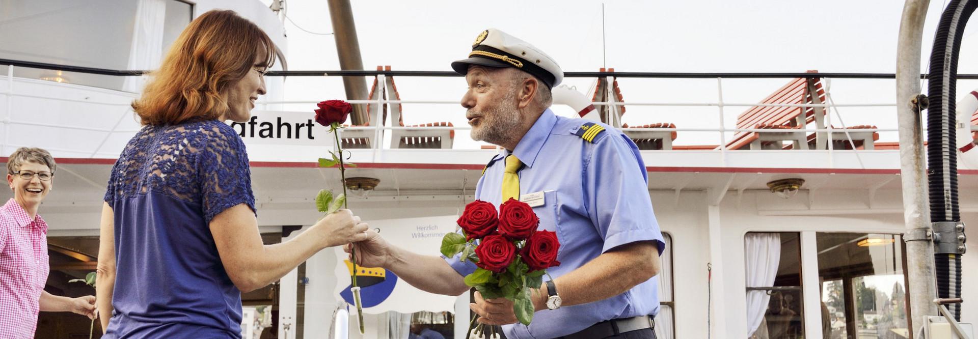 Käpitan der SGV schenkt einer Mutter eine rote Rose, bevor sie an Bord des Dampfschiffes geht.