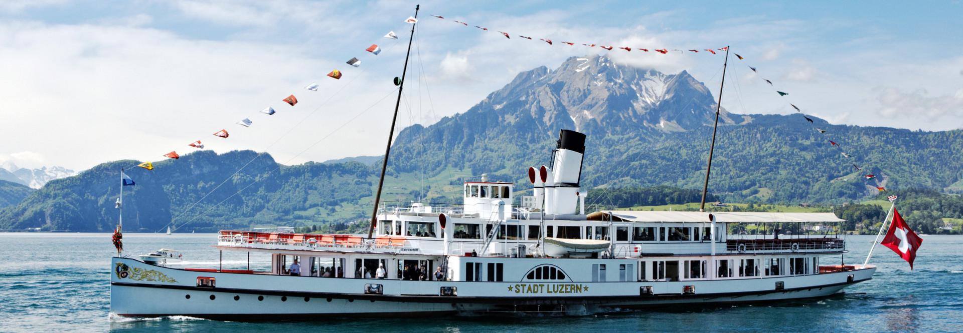 Das Dampfschiff Stadt Luzern seitlich vor dem Pilatus bei schönem Wetter.