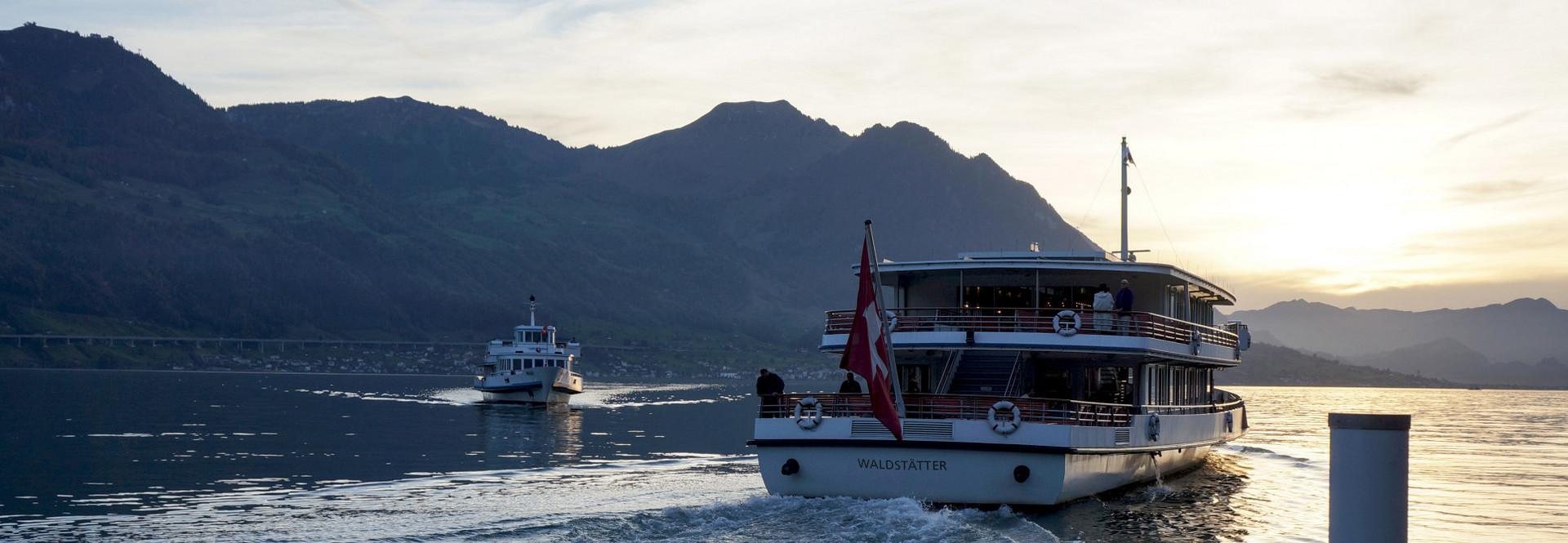 Zwei Motorschiffe der Schifffahrtsgesellschaft des Vierwaldstättersees kreuzen sich an einem Morgen auf dem Vierwaldstättersee.
