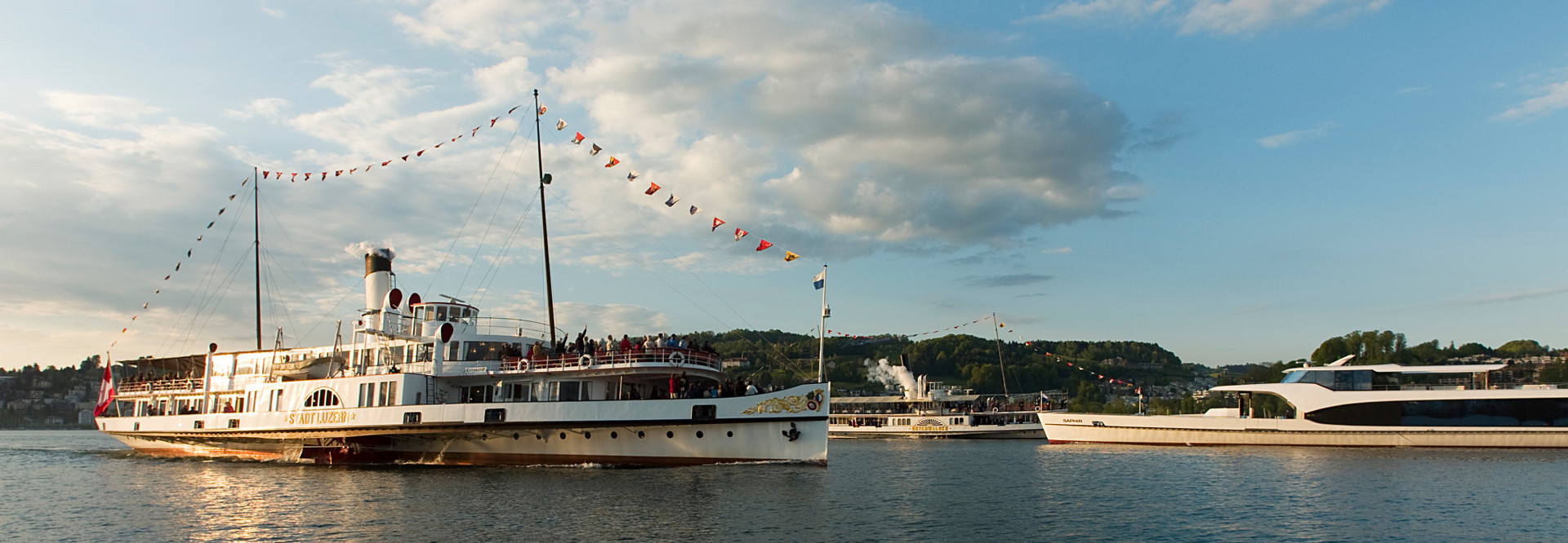 A steamboat and a motor vessel cross each other on Lake Lucerne.