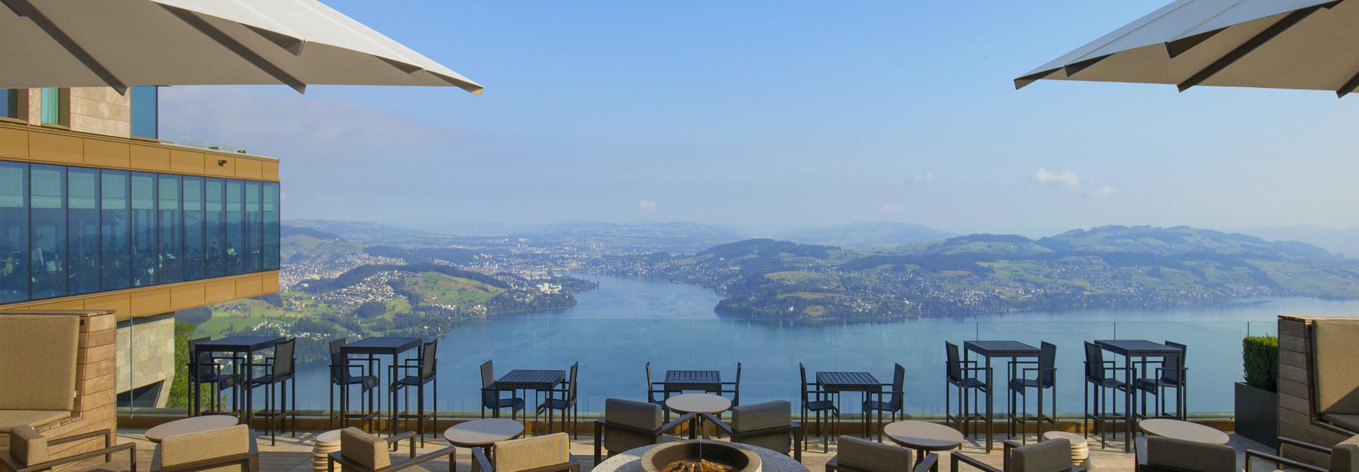 Die Tische und Stühle vom Restaurant Spices Terrace im Vordergrund und am Horizont der Vierwaldstättersee