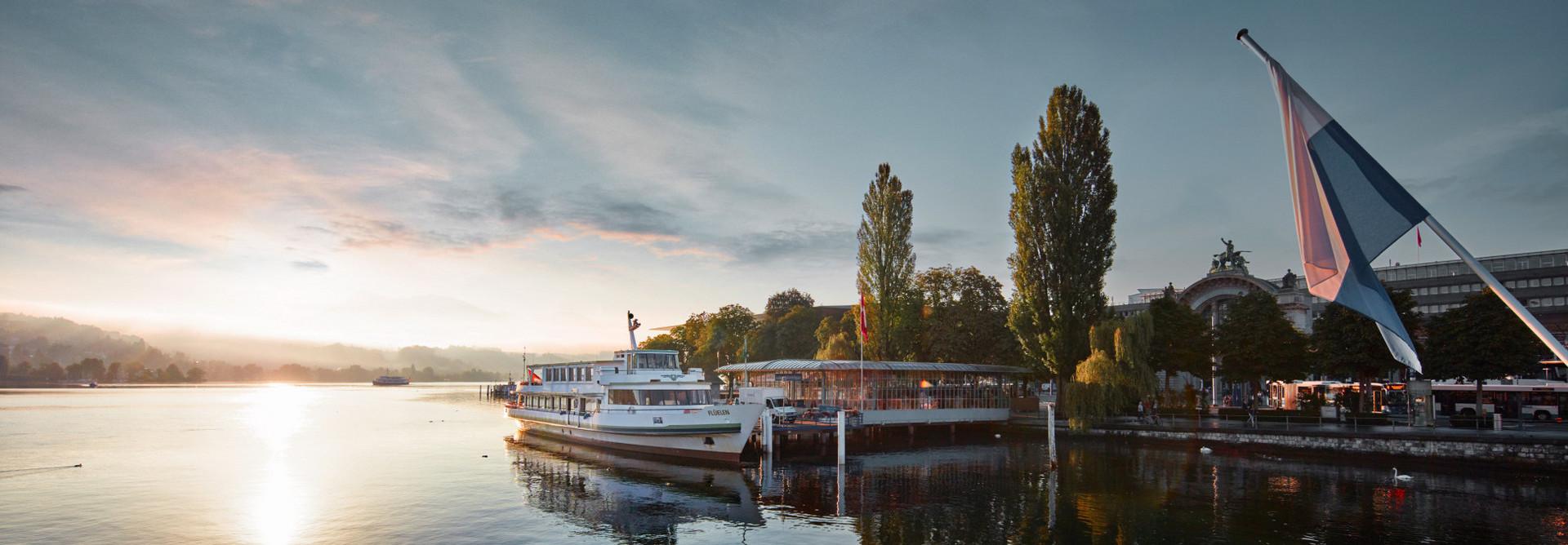 Sicht von der Seebrücke auf den Vierwaldstättersee. Die Sonne schimmert im See während ein Schiff am Steg in Luzern schwimmt.