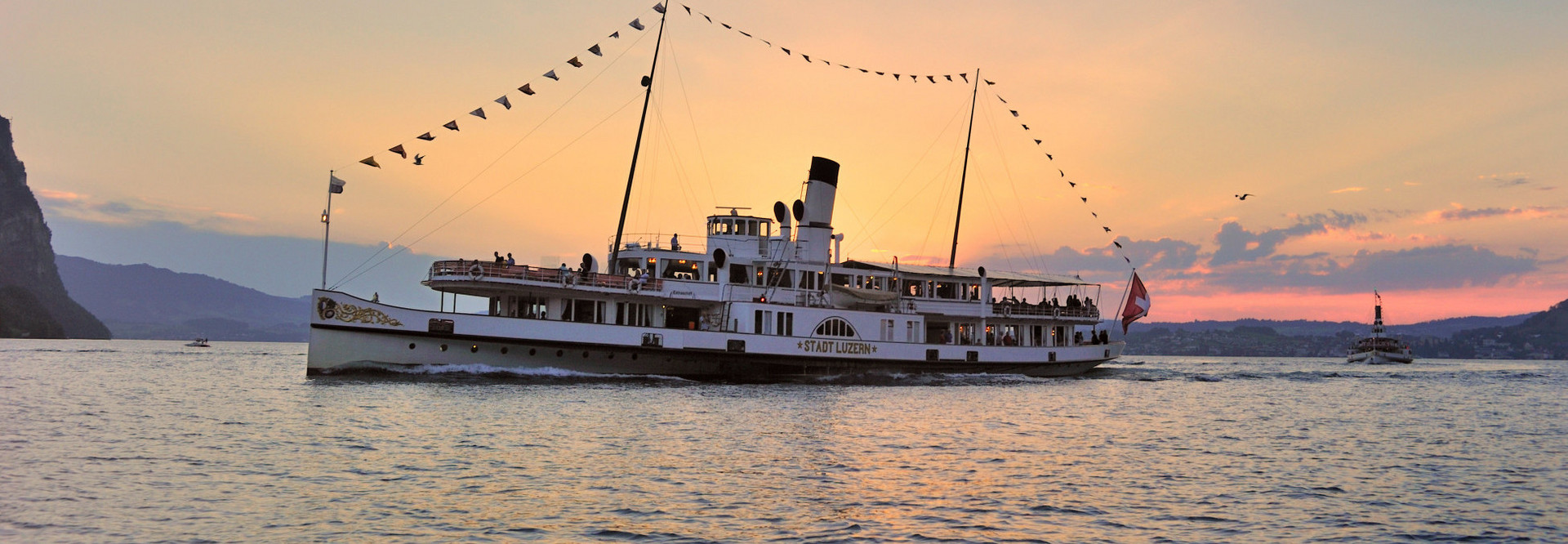 The steamship Stadt Luzern sideways during the trip. The sun sets behind the ship.