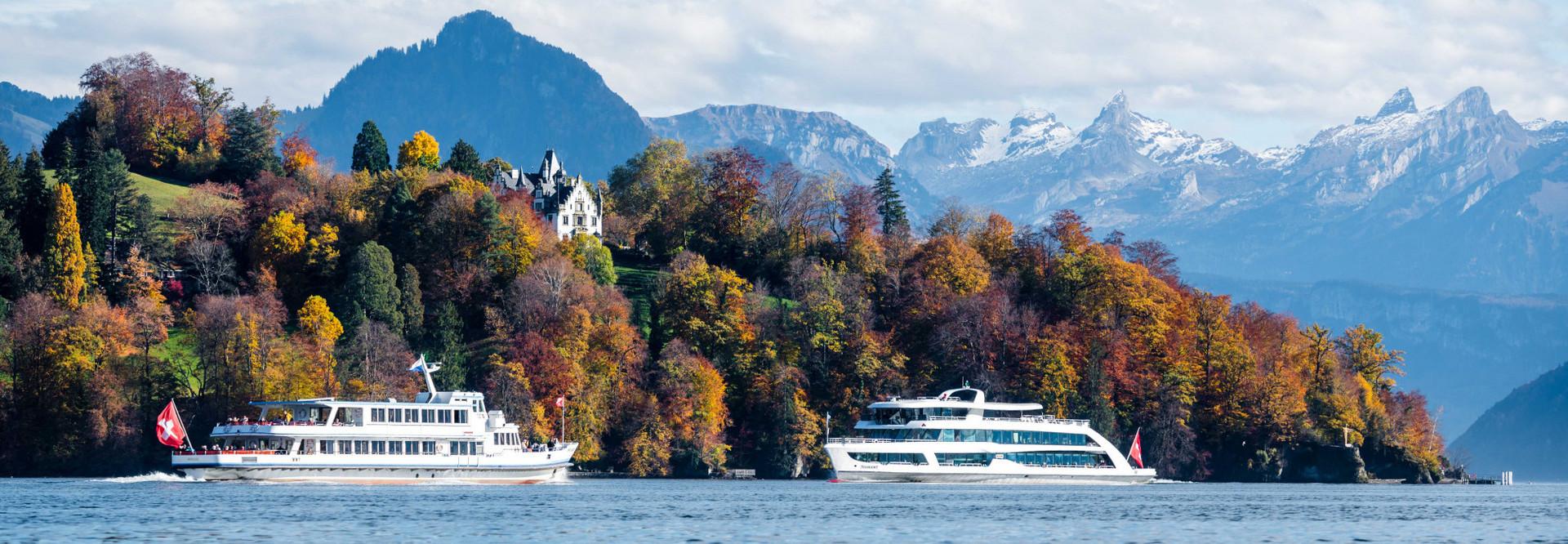 [Translate to English:] Zwei Motorschiffe kreuzen sich vor dem Meggenhorn - im Hintergrund sind die Berge sowie die schöne Herbststimmung zu sehen