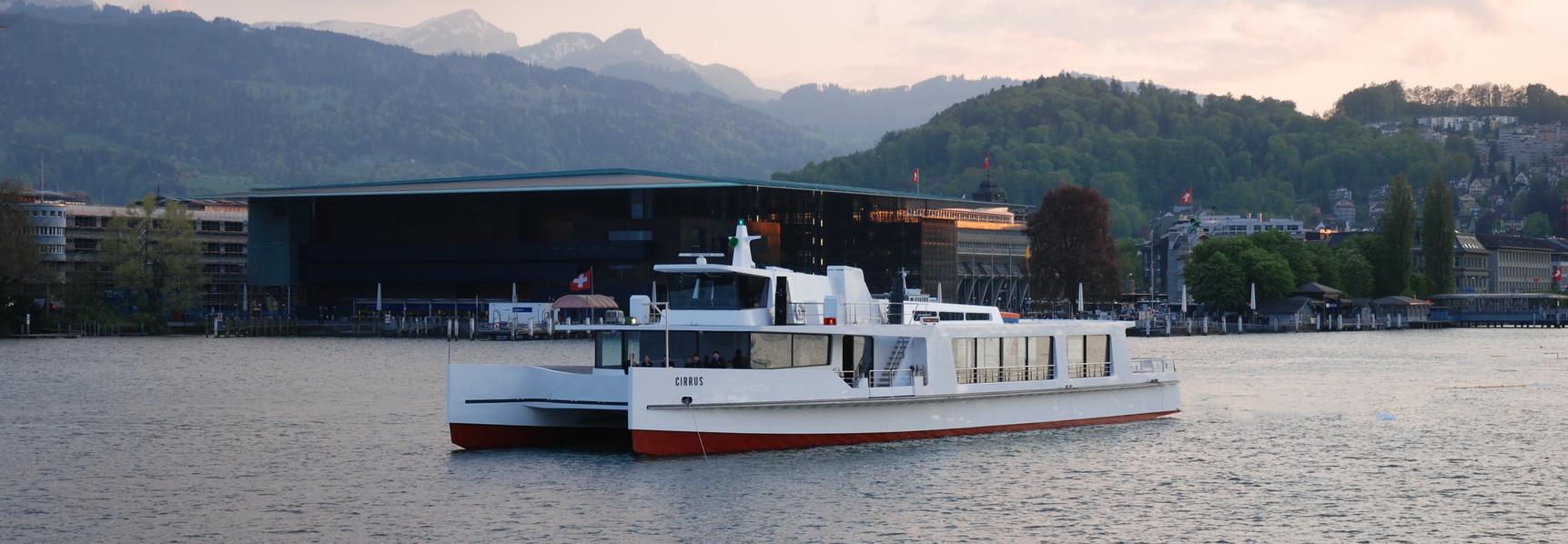 Bei bewölktem Wetter fährt das Motorschiff Cirrus im Luzerner Seebecken, im Hintergrund ist das KKL zu sehen.