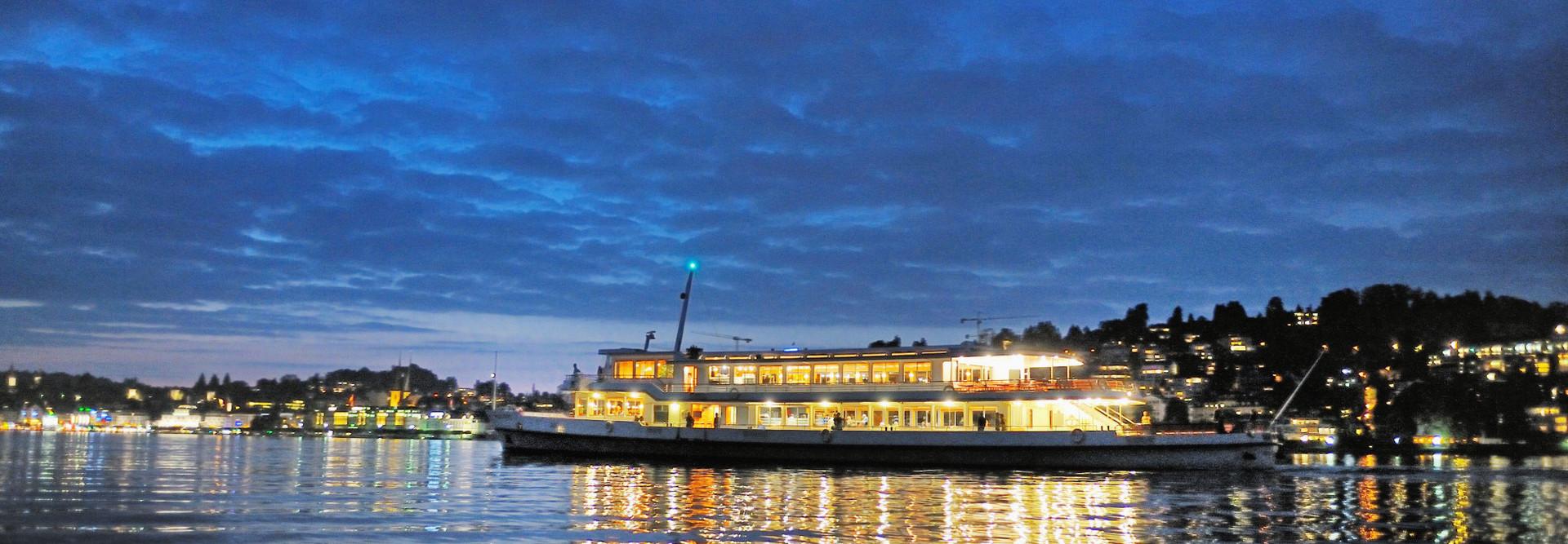 Man sieht ein Motorschiff am Abend auf dem See vor Luzern.