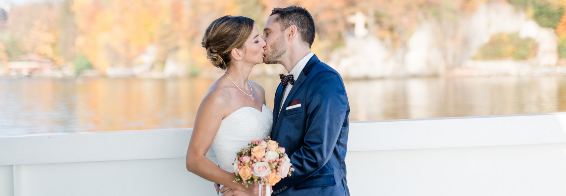 The bride and groom kiss outside on the ship. In the background the lake and the forest with coloured leaves can be seen blurred.