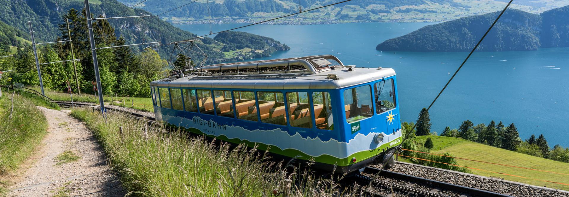 Eine blaue Rigi Bahn fährt die Rigi hoch mit dem Vierwaldstättersee im Hintergrund