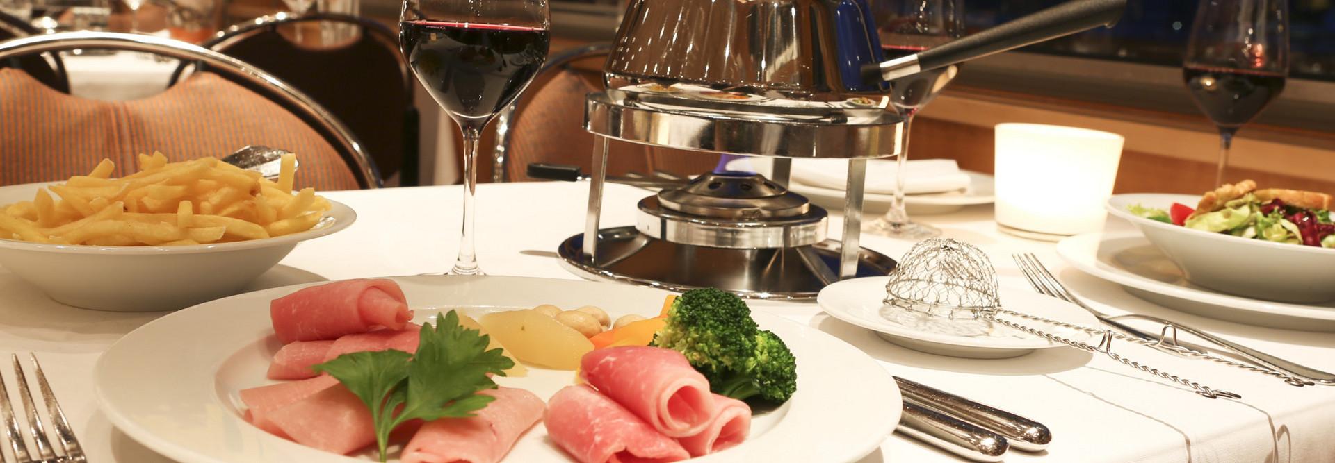 Ein Teller mit frischen Fleischstücken und einer Boillon für Fondue Chinoise