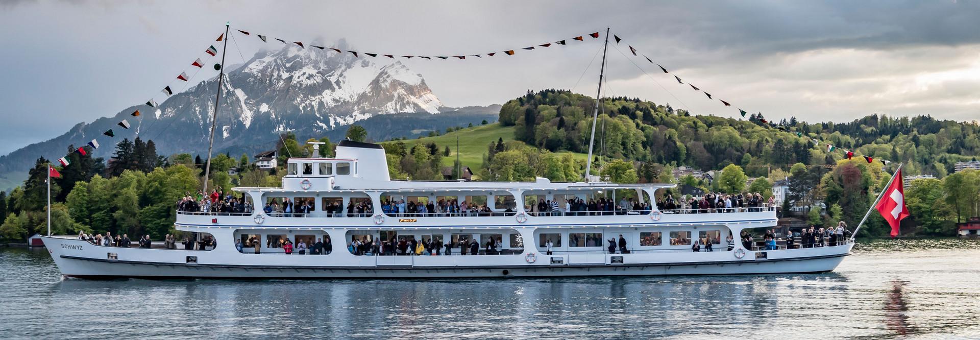 Le bateau à moteur Schwyz lors d'un voyage sur le lac des Quatre-Cantons. Plusieurs drapeaux fixes ornent le bateau à moteur. On peut voir le Pilatus en arrière-plan.
