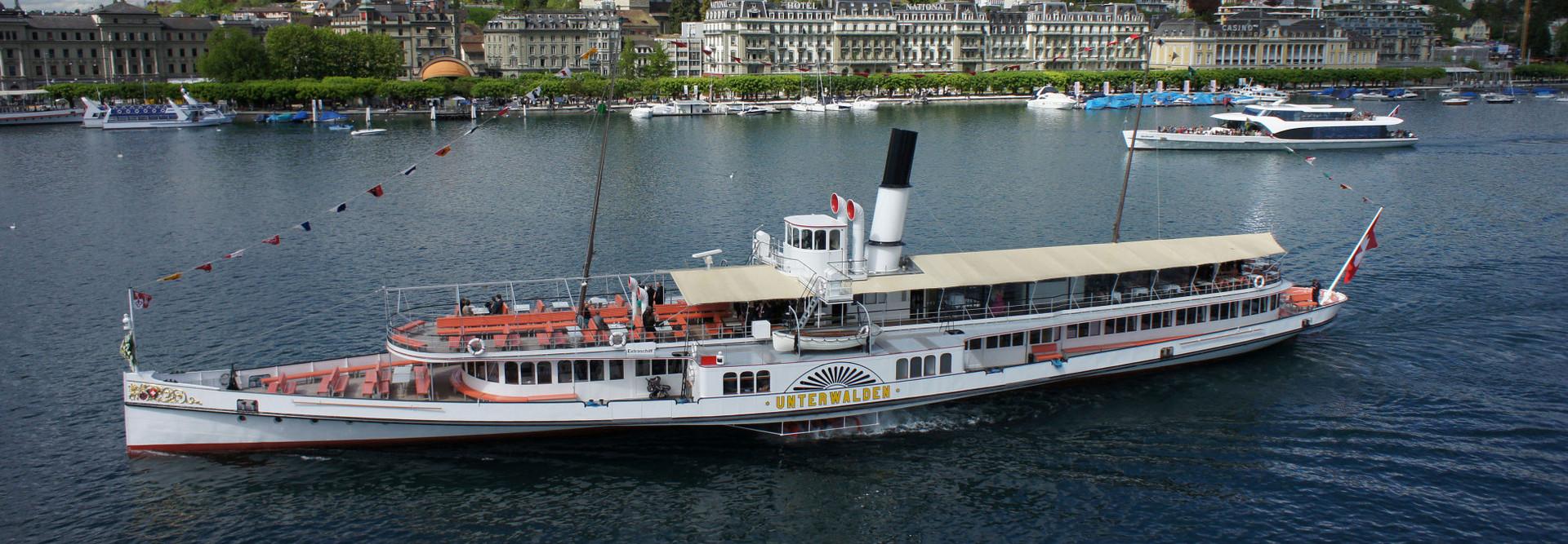 Seitliche Luftaufnahme des Dampfschiffes Unterwalden im Luzerner Seebecken. Der Himmel ist bewölkt.