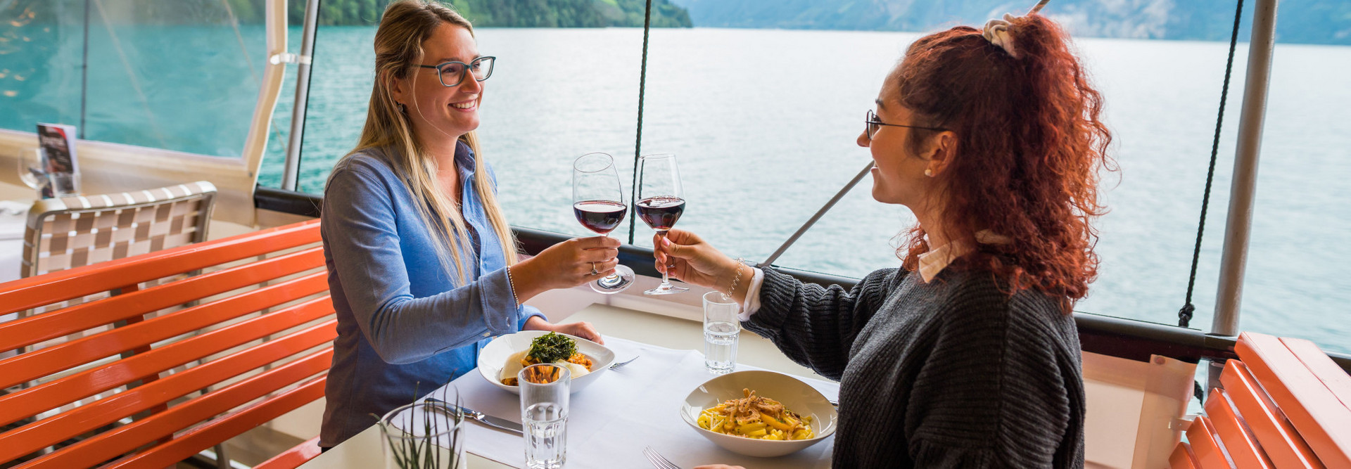Two young women enjoy the gastronomic offer on the ship and toast with a glass of red wine.