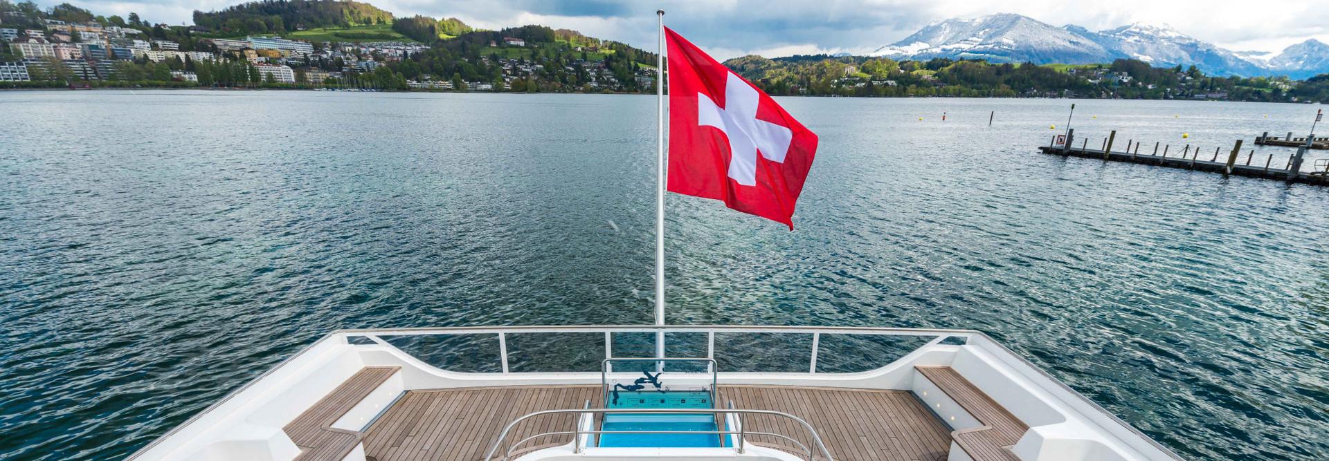 Sicht von oben auf das Heck von dem Motorschiff Diamant. Die Schweizer Fahne weht im Wind, der Himmel ist leicht bewölkt.