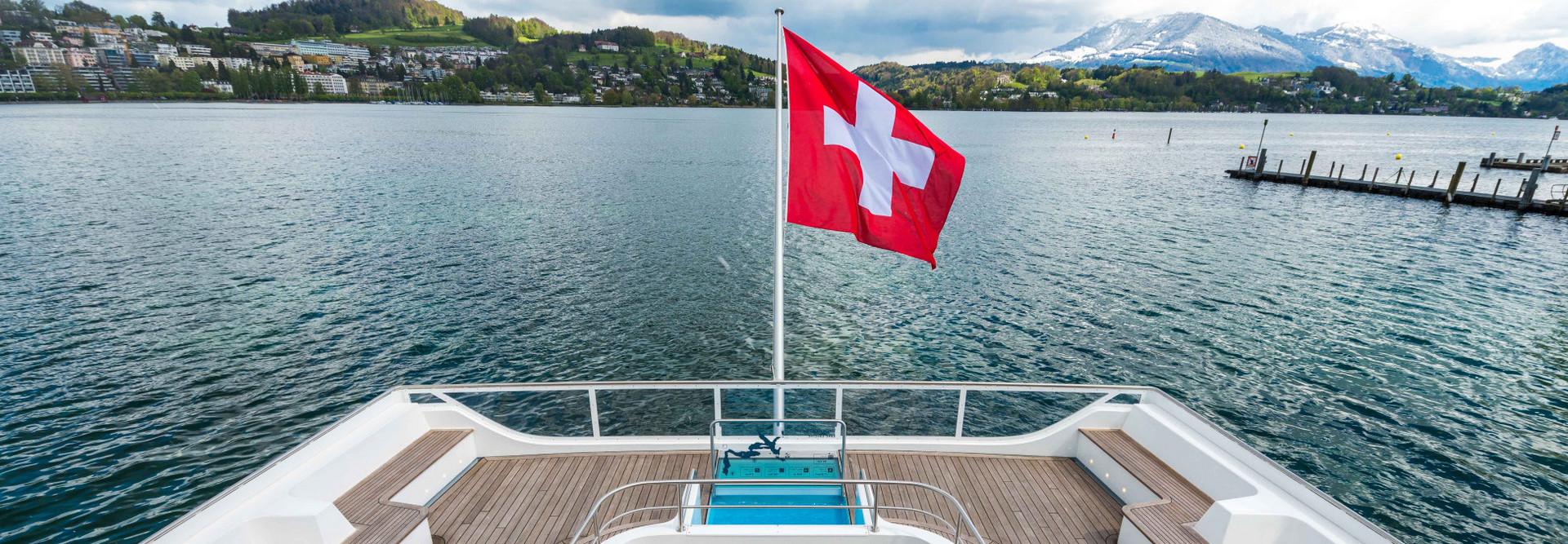 Vue de dessus de la poupe du bateau à moteur Diamant. Le drapeau suisse flotte au vent, le ciel est légèrement nuageux.