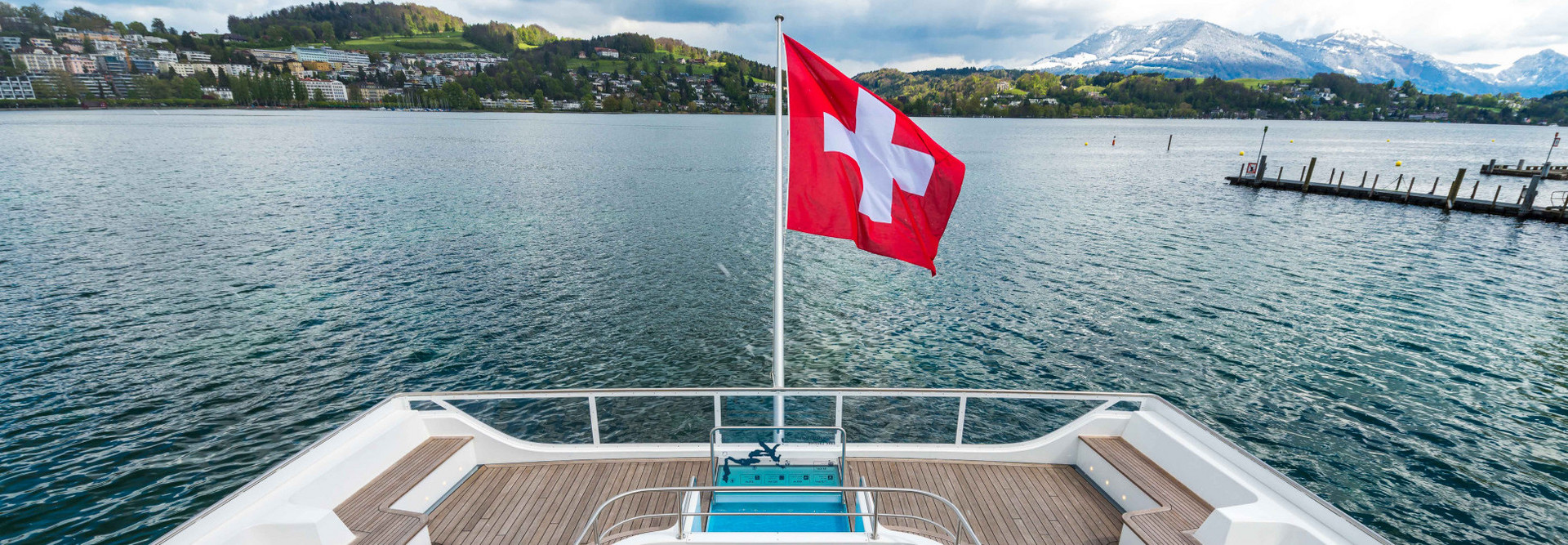 View from above on the stern of the motor ship Diamant. The Swiss flag is blowing in the wind, the sky is slightly cloudy.