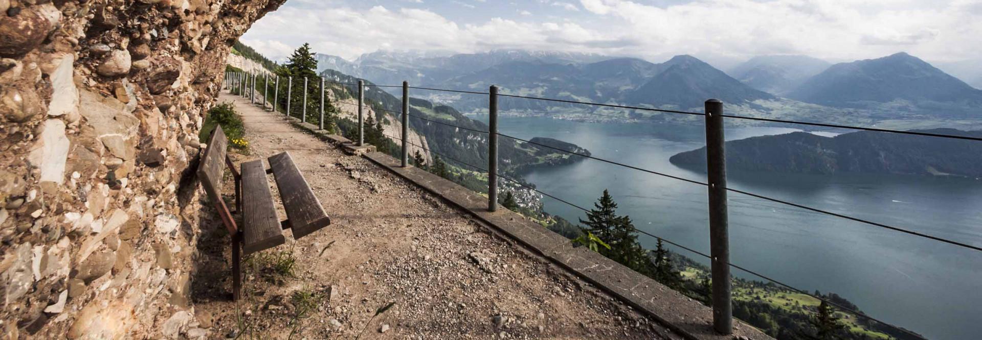 Man sieht den Wanderweg mit einer Sitzbank und rechts im Bild sieht man den Vierwaldstättersee.