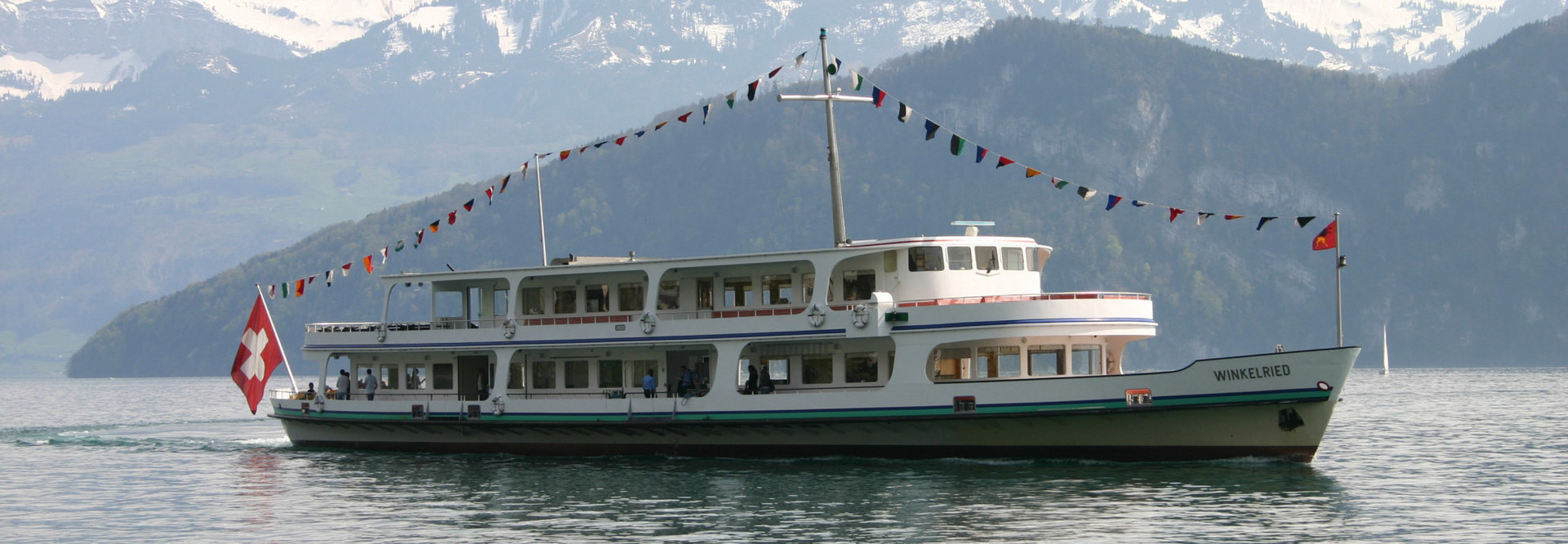 Während einer Fahrt auf dem Vierwaldstättersee, schmückt eine Festbeflaggung das Motorschiff Winkelried.