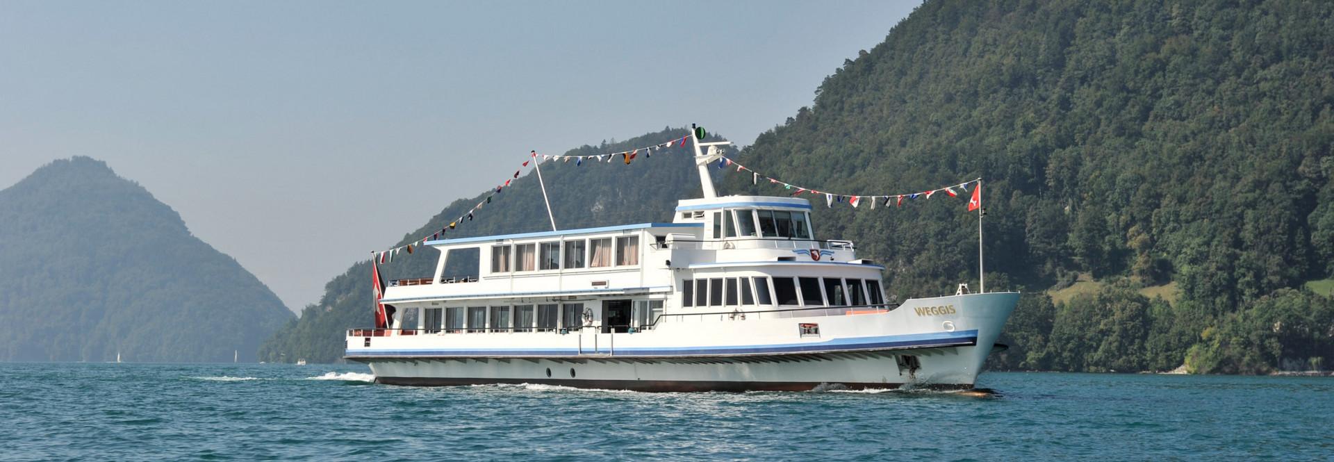 The motor vessel Weggis cruises on Lake Lucerne in sunny weather.