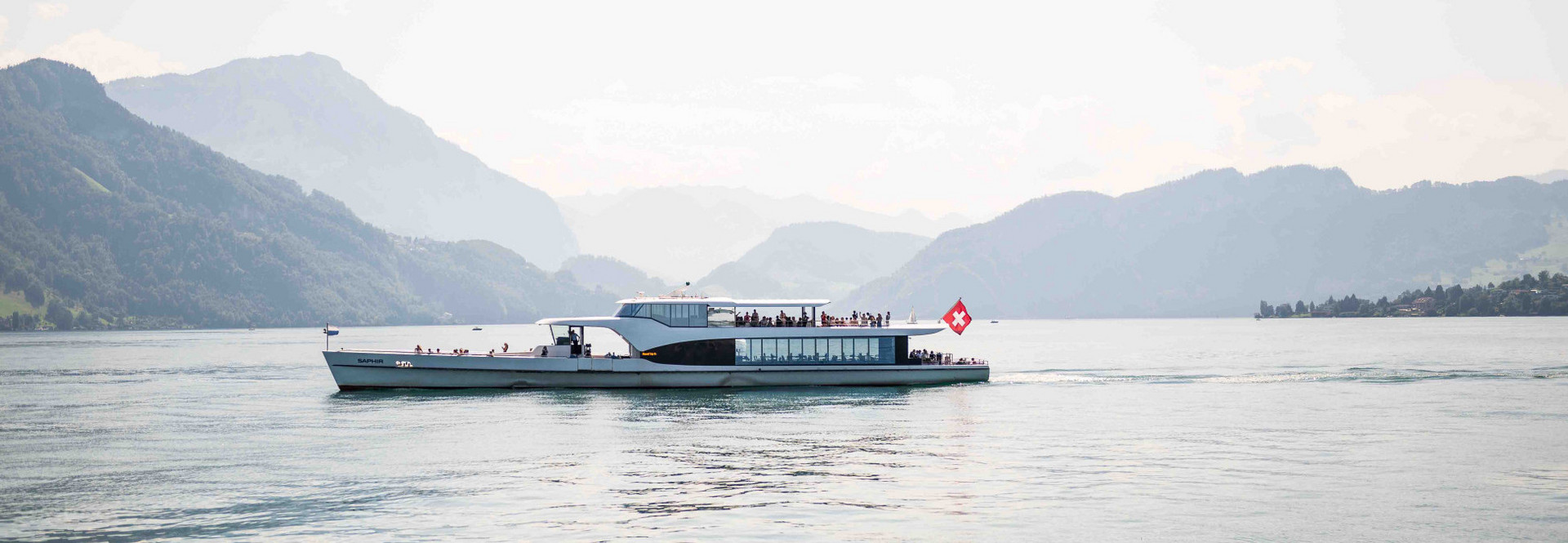 MS Saphir fährt mitten auf dem See und Gäste geniessen die 1-stündige Rundfahrt auf der Panorama-Yacht.
