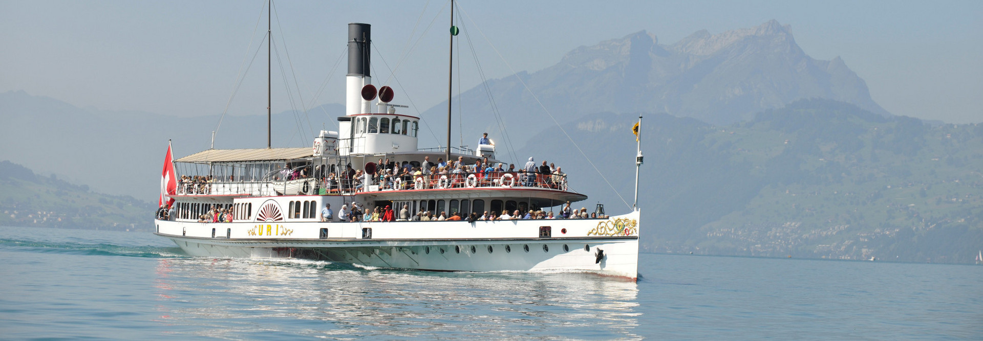 The steamship Uri sails in nice weather. In the background, the Pilatus can be seen.