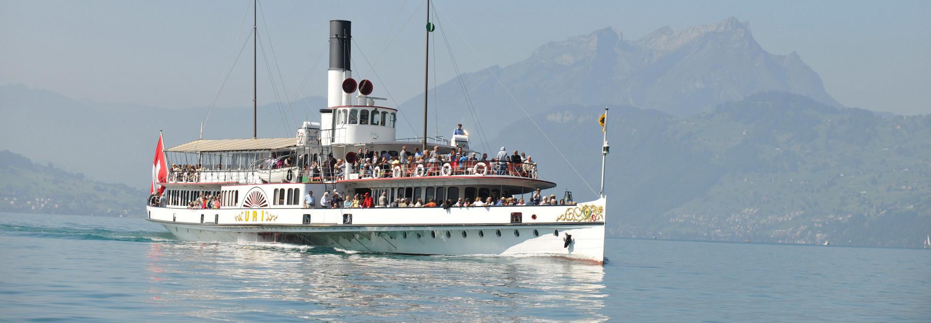 Le bateau à vapeur Uri navigue par beau temps. En arrière-plan, on peut voir le Pilatus.