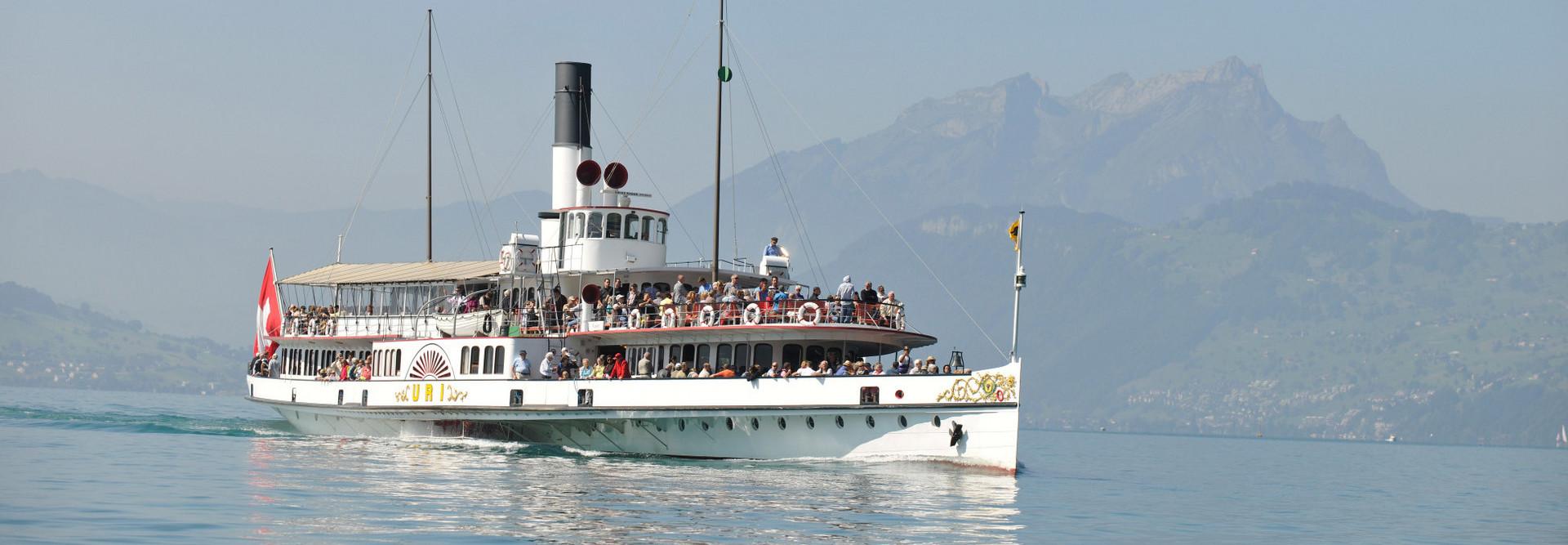 Das Dampfschiff Uri fährt bei schönem Wetter. Im Hintergrund ist der Pilatus zu sehen.