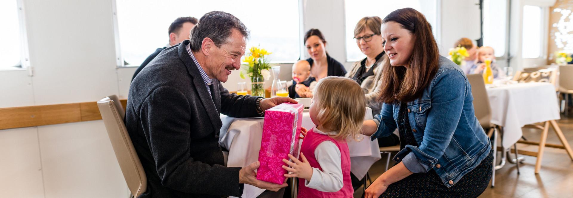 Familiengeburtstagsfeier auf dem Schiff. Ein kleines Mädchen übergibt dem Grossvater ein Geschenk.