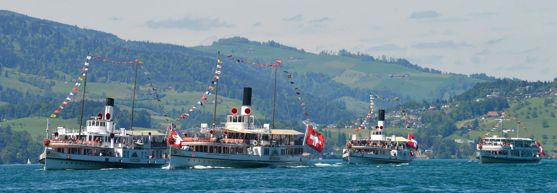 Dampfschiff-Parade mit Flieger im Hintergrund.