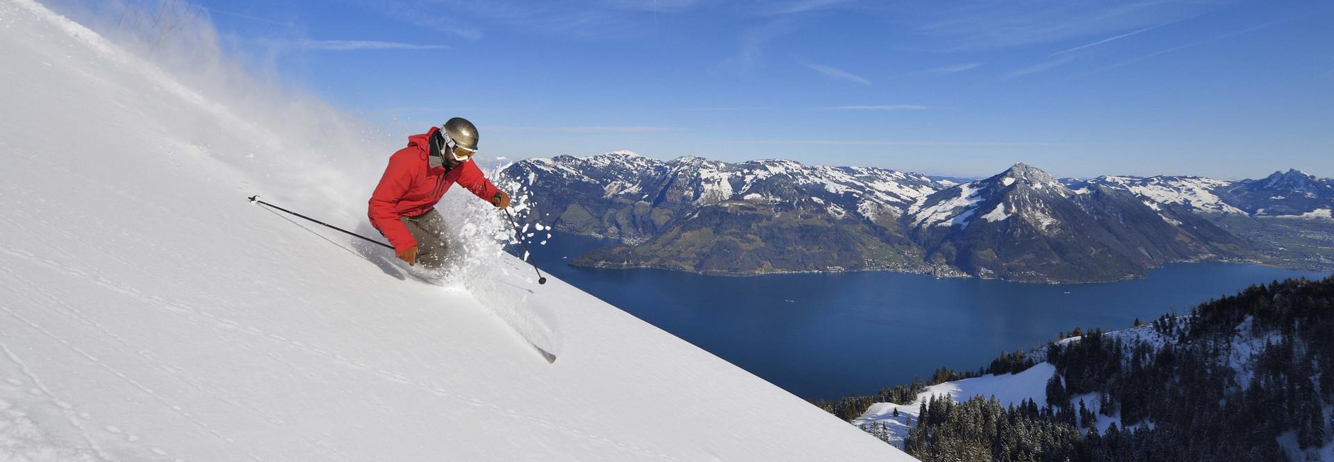Skifahrer fährt auf der Klewenalp die Piste herunter, im Hintergrund ist der Vierwaldstättersee zu sehen.