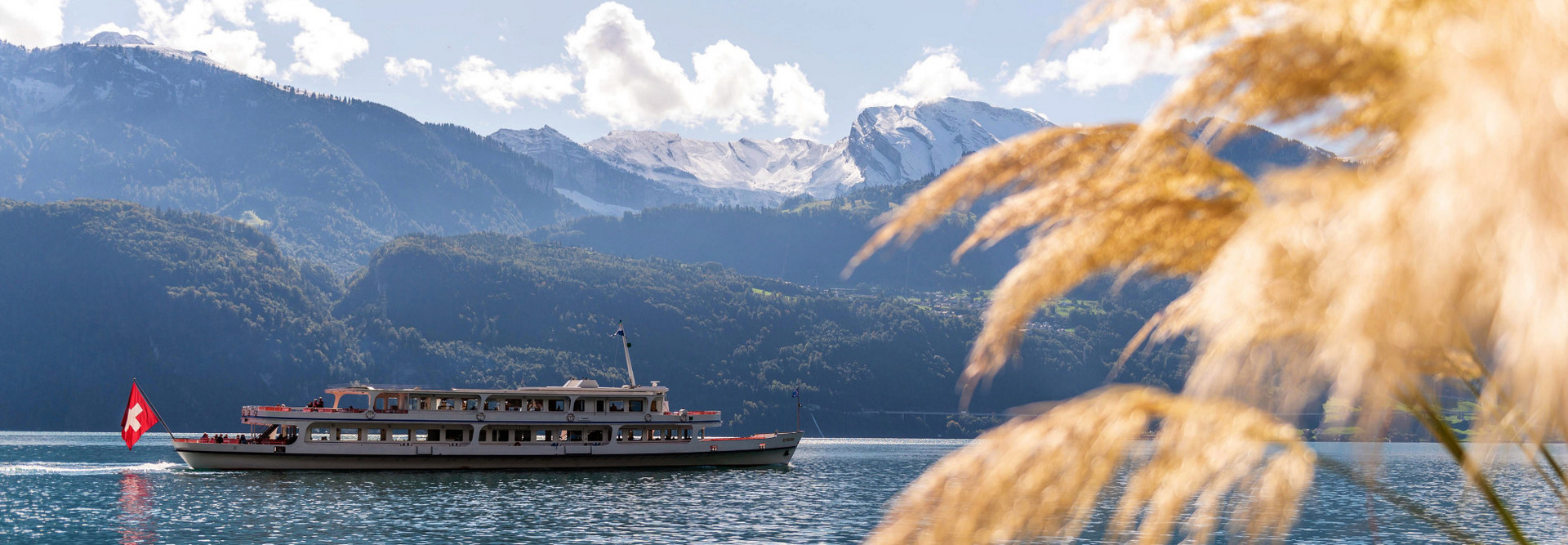 Motorschiff Europa fährt an einem Herbsttag an frisch verschneiten Bergen vorbei.