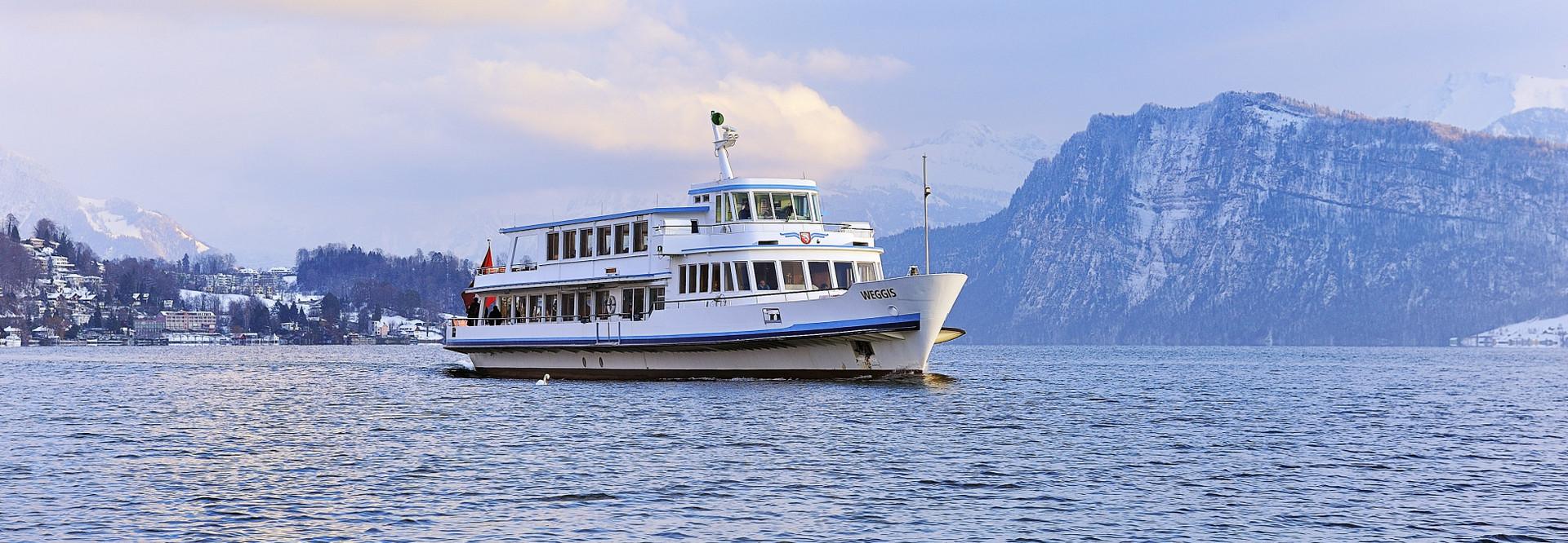 Un bateau à moteur navigue sur le lac des Quatre-Cantons en hiver.