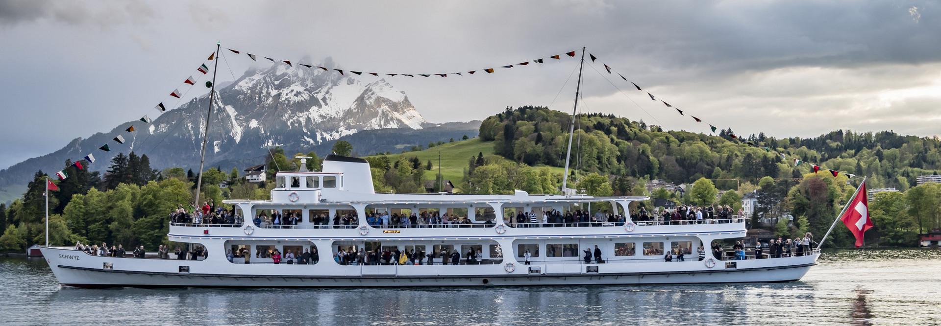 Private Feier auf einem fahrenden Schiff mit Festbeflaggung. Im Hintergrund ein gründer Hang sowie der Pilatus zu sehen.