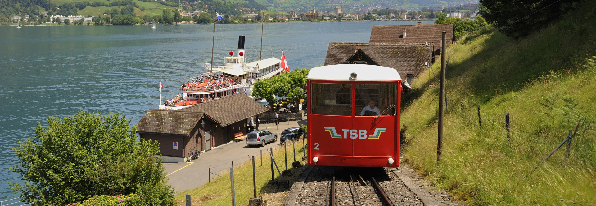 Die rote Treib Seelisberg Bahn fährt den Berg hoch. Unten ist ein Dampfschiff zu sehen